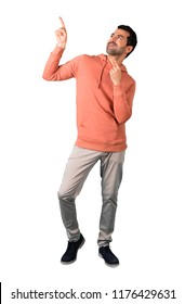 Full body of Man in a pink sweatshirt pointing with the index finger a great idea and looking up on isolated white background