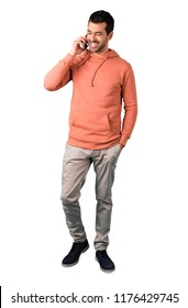 Full body of Man in a pink sweatshirt keeping a conversation with the mobile phone with someone on isolated white background. Ideal for use in architectural designs