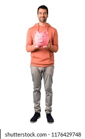 Full body of Man in a pink sweatshirt taking a piggy bank and happy because it is full on isolated white background