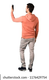 Full body of Man in a pink sweatshirt taking a selfie with the mobile on isolated white background. Ideal for use in architectural designs