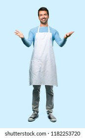 Full body of Man wearing an apron presenting and inviting to come with hand. Happy that you came on blue background