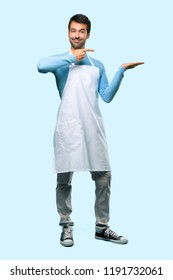 Full body of Man wearing an apron holding copyspace imaginary on the palm to insert an ad on blue background