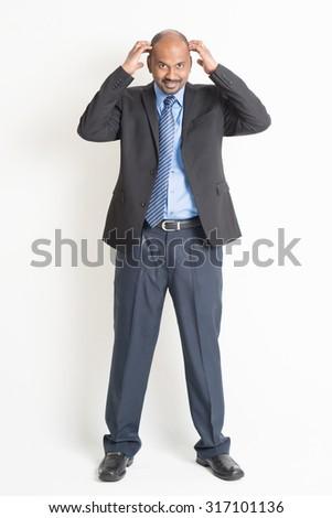 4cd31b2cc Full body mature Indian business man hands scratching his bald head
