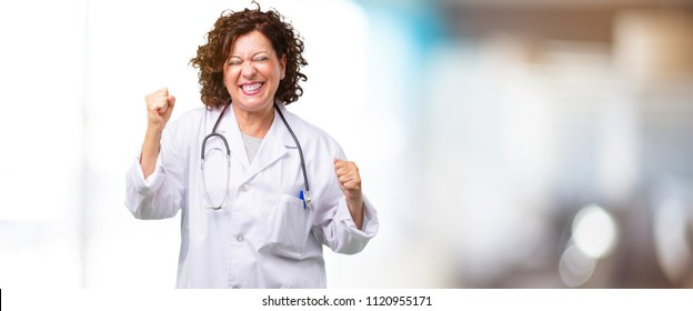 Full body middle age doctor woman very happy and excited, raising arms, celebrating a victory or success, winning the lottery