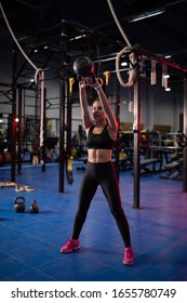 Full body muscular female athlete in sportswear doing swing exercise with kettlebell during functional training in contemporary gym