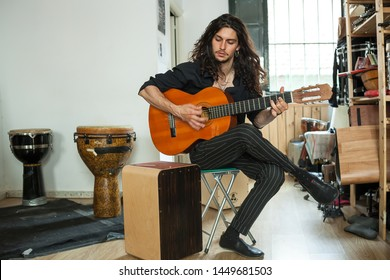 Full body music shot of a flamenco Styled young long haired musician passionately playing the spanish acoustic guitar on a humble rehearsal studio with more percussion instruments.