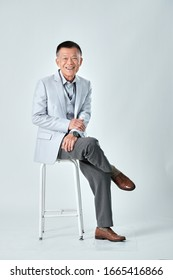 Full body of an old asian man wear light grey suit sitting on a grey chair and cross one's legs in studio white background. Isolated picture of happiness asian old man.
