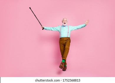 Full body photo of active grandpa moving dance senior party raise up walk stick leg wear mint shirt suspenders bow tie pants shoes green socks isolated pink pastel background