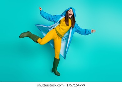 Full body photo of attractive funny lady cheerful mood rainy weather street walk hood on head many puddles raise leg wear raincoat sweater pants gum boots isolated teal color background