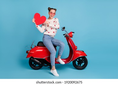 Full body photo of brunette bun hairstyle woman sit motorbike hold big red paper heart isolated on blue color background