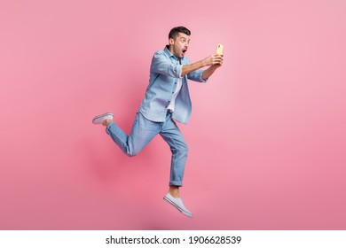 Full body photo of brunette man hold phone amazed news run jump wear casual outfit isolated on pink color background