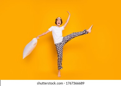 Full body photo of cheerful lady hold big pillow wake up playful mood dancing energetic raise leg up wear mask white t-shirt plaid pajama pants barefoot isolated yellow color background