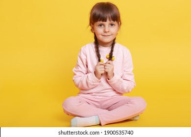 Full body photo of coy kid sitting with crossed legs, wearing casual outfit isolated over yellow background, keeping hands on her pigtails, looks at camera with timid expression.