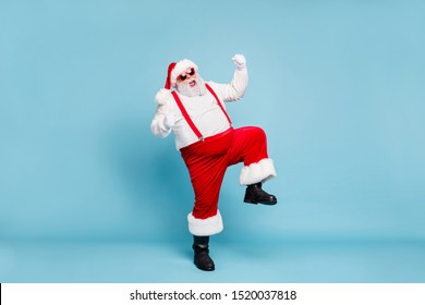 Full body photo of crazy funny funky fat santa with big belly raise fists scream yeah enjoy christmas party wear red pants style stylish boots overalls spectacles isolated over blue color background