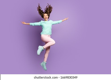 Full body photo of crazy funny cute girl jump hold hands enjoy win blowing in her haircut wear pink trousers soft pastel pullover footwear isolated over violet color background