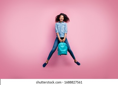 Full body photo of excited funky afro american girl rest relax after college study hold bag wear casual style sneakers isolated over pink color background