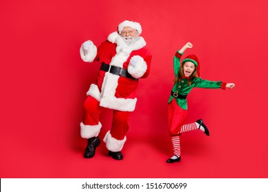 Full body photo of excited two santa claus in hat headwear dancing on festive event  wearing green bright costume isolated over red background