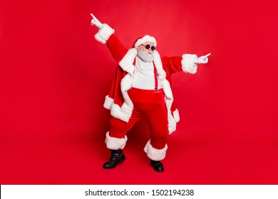 Full body photo of funky fat santa claus with big funny abdomen dancing raising arms wearing style stylish trendy eyewear eyeglasses isolated over red background