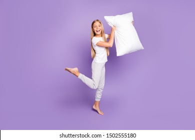 Full body photo of funny funky crazy emotions blonde hair girl barefoot hold pillow want play game sleep-over party with best friends sisters wear white t-shirt pants isolated purple color background