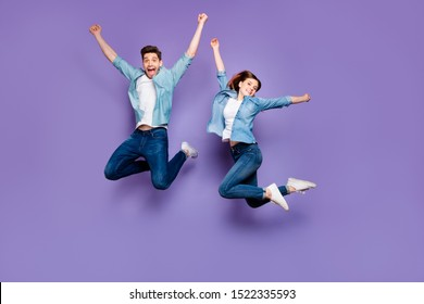 Full body photo of funny funky crazy cheerful married students with brown hair redhair jump have relax spring holidays date raise hands wear youth clothes isolated over purple color background
