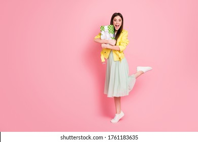 Full body photo of funny lady hold hands close to chest large green giftbox overjoyed amazing surprise wear yellow leather jacket long skirt shoes isolated pastel pink color background