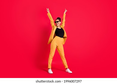 Full body photo of funny lady stand wear eyewear yellow suit isolated on vivid red color background