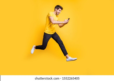 Full body photo of handsome guy jumping high holding telephone rushing romantic date typing girlfriend sms wear casual t-shirt trousers isolated yellow color background