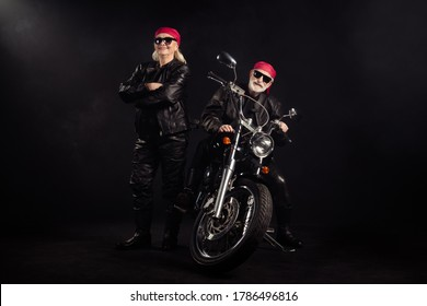 Full body photo of old bikers man lady couple drive chopper travel feel young rock moto festival arms crossed wear rocker leather outfit sunglass bandana isolated black color background