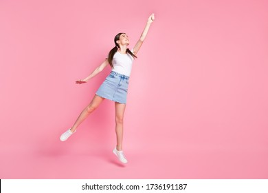 Full body photo of pretty lady jump high catch imagine umbrella flying up with wind wear casual white t-shirt mini denim skirt shoes isolated pastel pink color background