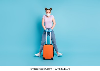 Full body photo of pretty lady use respirator pass check-airport hold rolling case fly home parents viral control playful mood wear t-shirt jeans shoes gloves isolated blue color background
