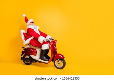 Full body photo of santa white hair grandpa riding speed x-mas party by bike afraid to be late wear trendy sun specs red coat trousers cap shirt boots isolated yellow color background