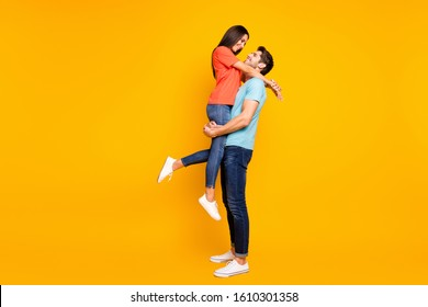 Full body photo of two cute people couple guy holding carrying lady look eyes lovely weekend romance moment wear casual blue orange t-shirts jeans isolated yellow color background