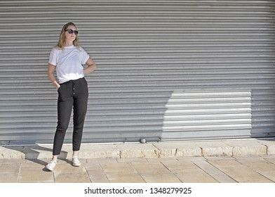 Full body photo of young casual sporty dressed blonde woman with sunglasses in white t-shirt against corrugated iron wall street style