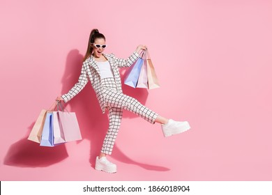 Full body photo of young excited happy positive smile girl hold bags go shopping buy wear jacket pants isolated over pastel color background