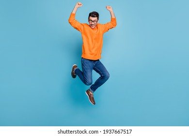 Full body photo of young excited man happy positive smile jump up rejoice victory isolated over blue color background