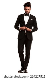 full body picture of an elegant man in tuxedo unbuttoning his coat on white background