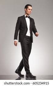 full body picture of an elegant man in tuxedo walking in studio, side view picture on grey background