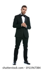 full body picture of elegant young businessman in black tuxedo holding hands and posing isolated on white background in studio