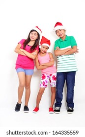 Full body picture of happy asian kids wearing Santa hat.
