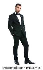 full body picture of sensual unshaved businessman in black tuxedo holding hands in pockets and posing isolated on white background in studio
