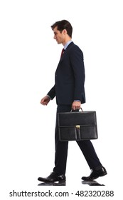 full body picture of a  young business man walking forward and holding a briefcase, isolated on white background