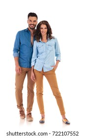 full body picture of young casual couple standing and smiling together on white background