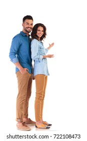 full body picture of young casual couple presenting something on white background