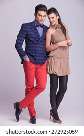 Full body picture of a young fashion couple posing together on grey studio background.