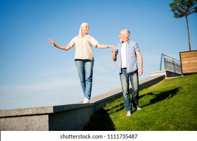 Full body portrait of active modern grandma and granddad walking outside handsome man leading by the hand pretty woman enjoying blue sky good weather sunny day