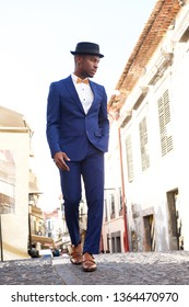 Full body portrait of african american male model in vintage suit and hat walking in city