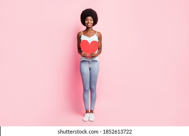 Full body portrait of attractive curly person hands hold heart symbol blue tank-top isolated on pink color background