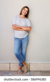 Full body portrait of attractive senior woman smiling with arms crossed