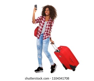 Full body portrait of attractive young african american girl walking with suitcase and taking selfie