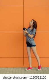 Full Body portrait of a beautiful girl with old film camera looking up on orange wall background